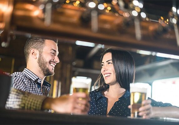 Young couple at beginnings of love story - Pretty woman drinking beer with handsome man at pub - Relationship lovers concept with drunk boyfriend and girlfriend together at brewery - Warm retro filter